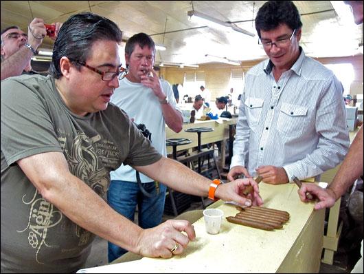 Rafael and Joshe demonstrate cigar rolling styles.